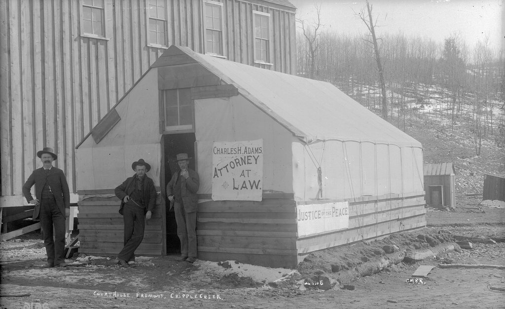 Courthouse, Fremont, Cripple Creek. Three men stand in front of canvas tent on wooden frame with sign 'Charles H. Adams, Attorney at Law', sign on side 'Justice of the Peace'. Colorado, 1892 or 1893