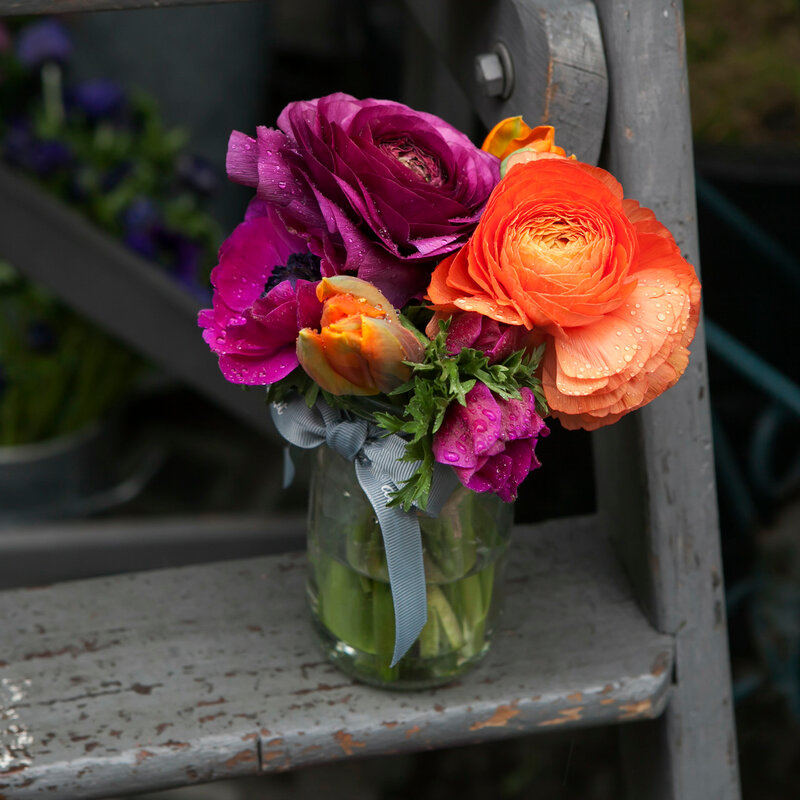 Spring bouquet with purple  ranunculus, orange tulips and anemones in a glass jar on the stair