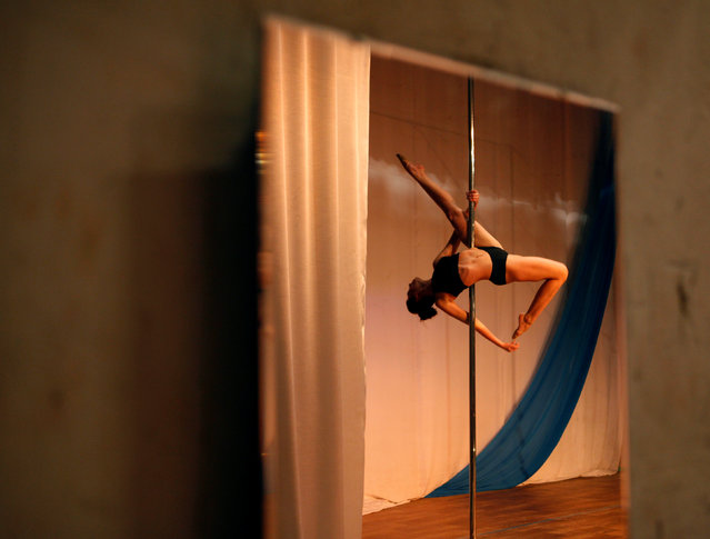 A participant is reflected in a mirror as she competes in the Perfect Pole 2016 pole dance champions