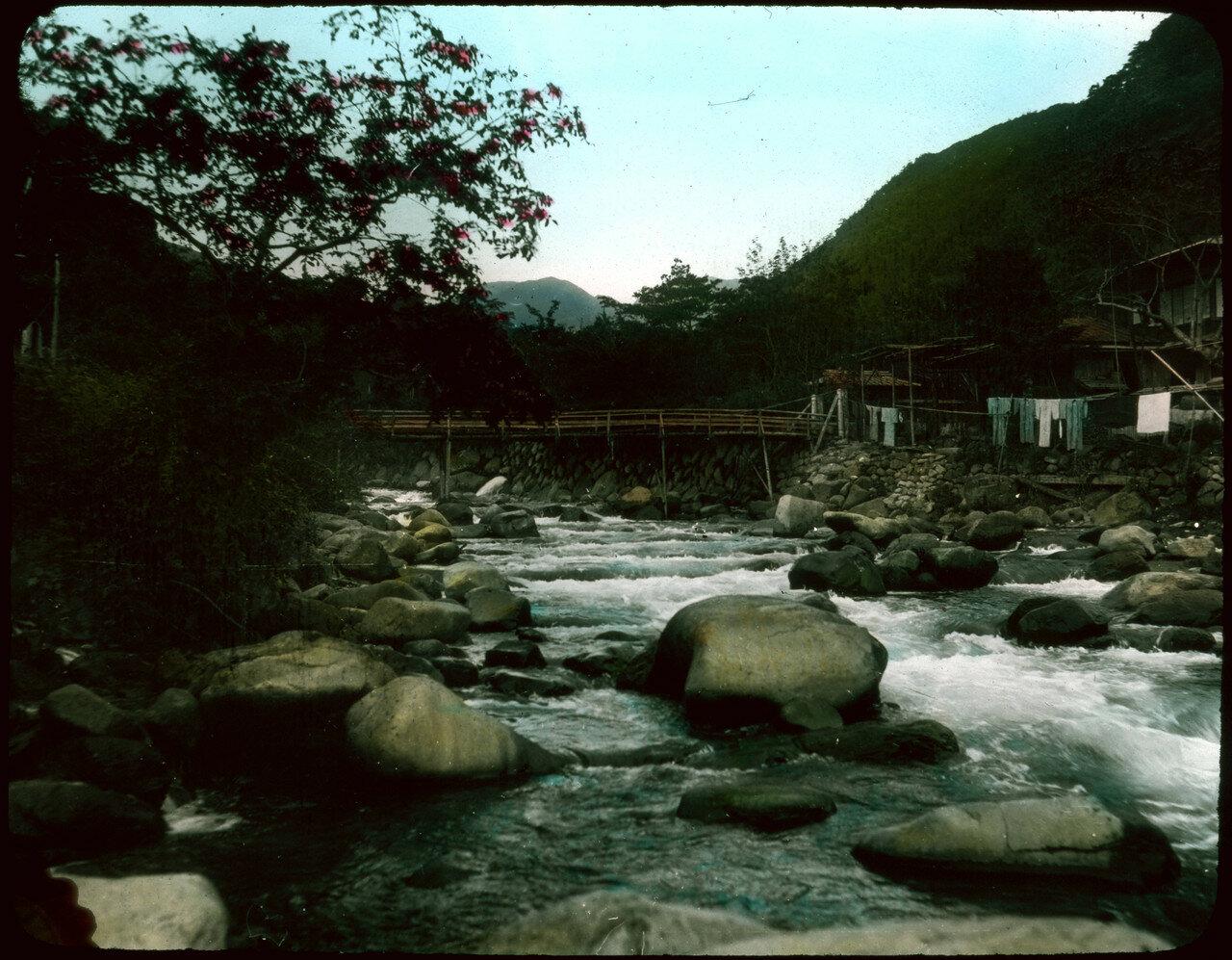 Дома вдоль берега усыпанной валунами реки