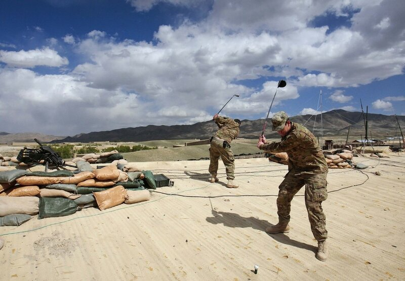 U.S. Army soldiers of 3/1 AD Task Force Bulldog prepare to hit golf balls from the rooftop of a building at Combat Outpost Boston in Kherwar district in Logar province