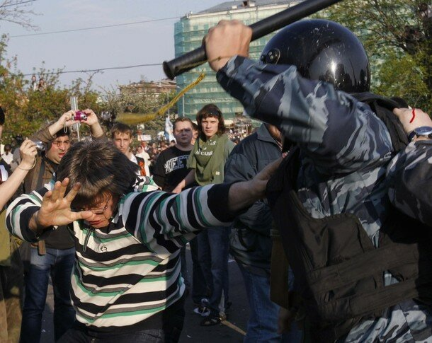 Russian riot police scuffle with protesters during the