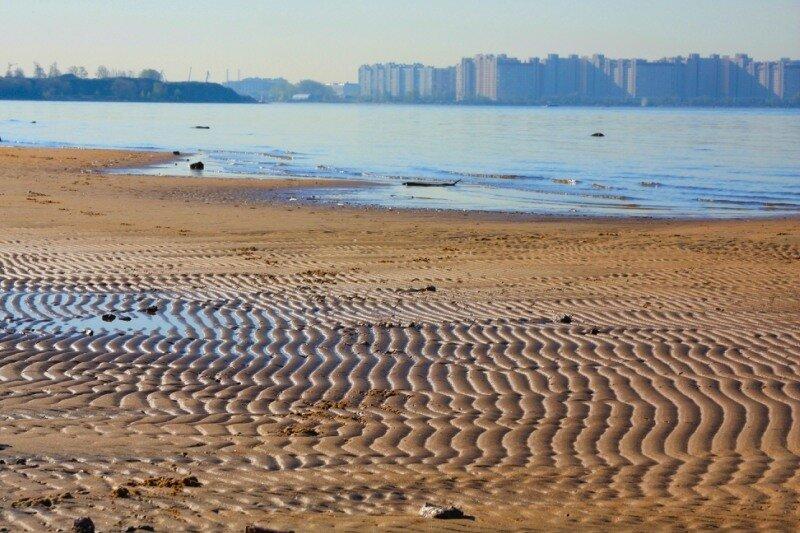 следы на песке с видом на Васильевский остров