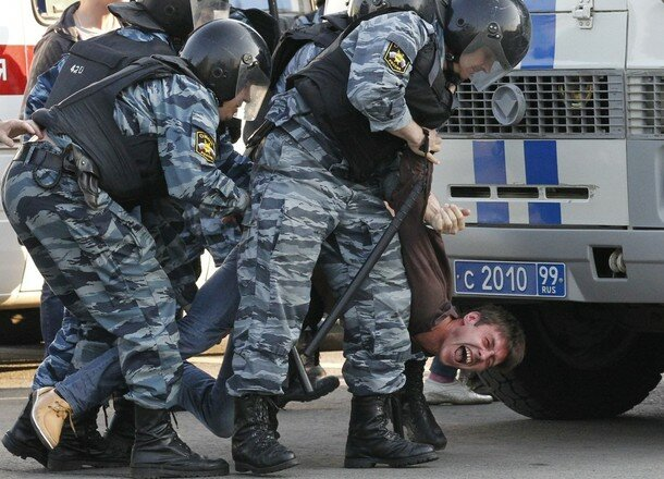 Russian riot police detain a protester during the