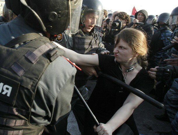 A participant is restrained by Russian riot police during the