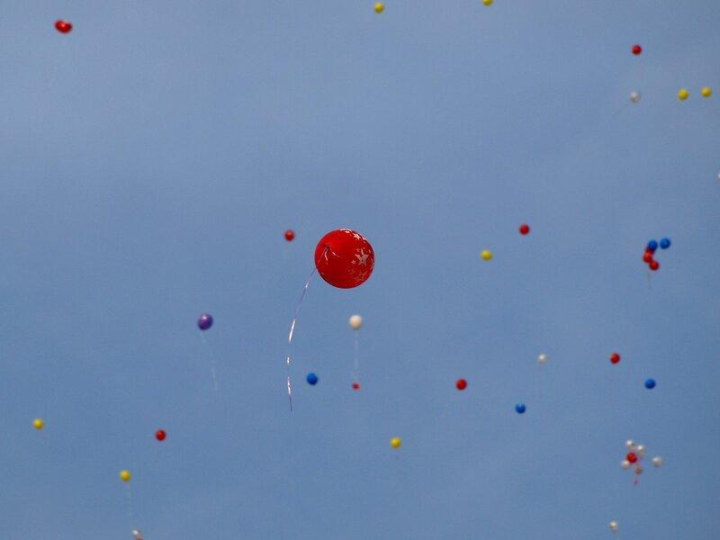 воздушные шары в небе и одинокий красный шарик