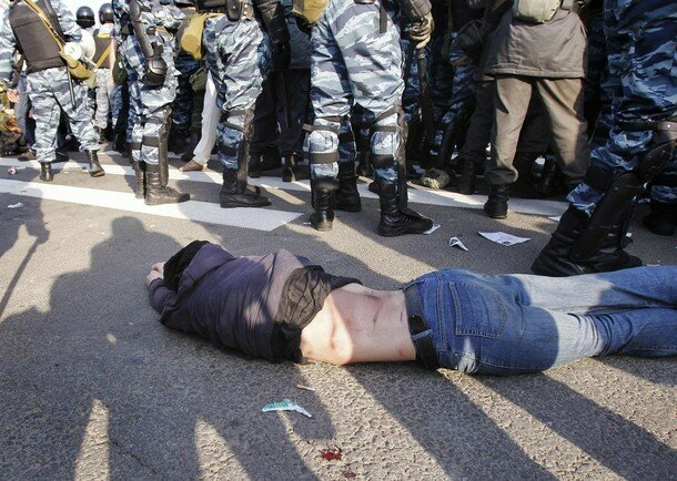 An injured protester lies on the ground next to Russian riot police during a scuffle at the