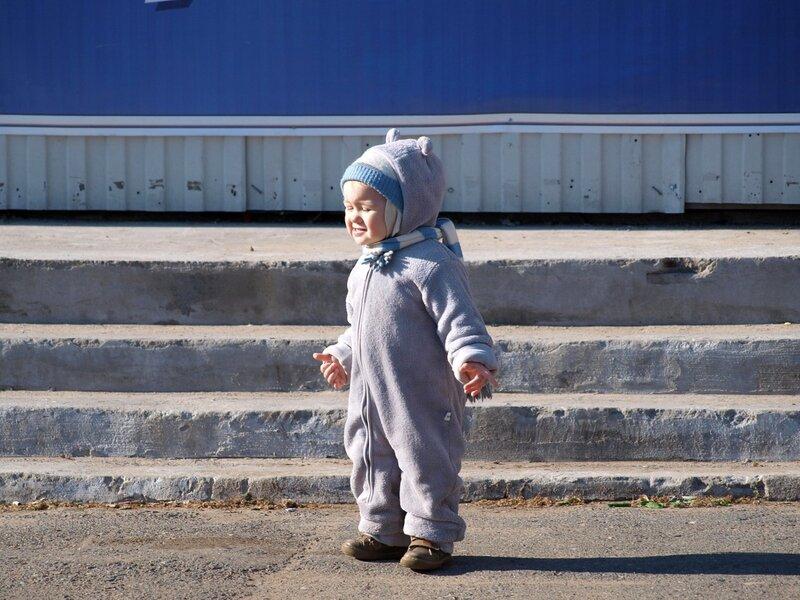 танциющий ребенок в комбинезоне с ушками