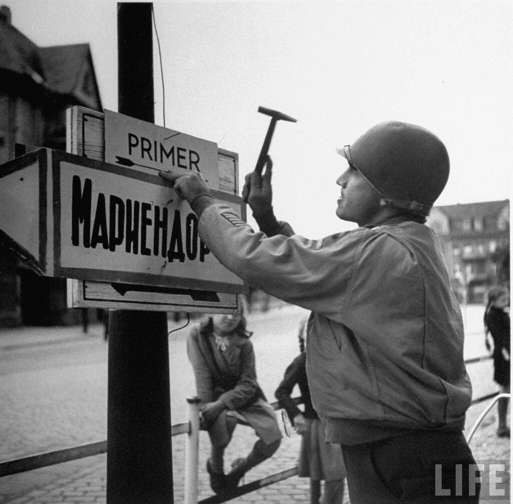 американский капитан прибивает вывеску для русских солдат
