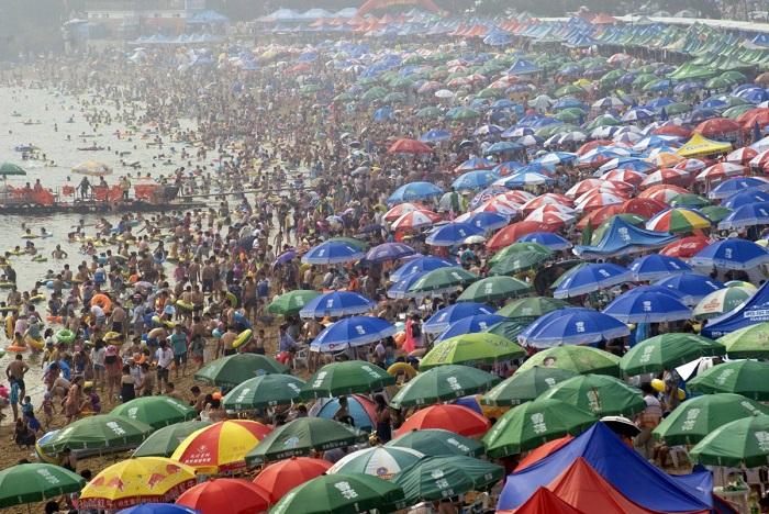 Люди толпятся на пляже в городе Далянь, провинция Ляонин, спасаясь от летней жары. 16. Туристический