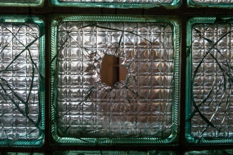 отверстие в стеклянном плитке на стене