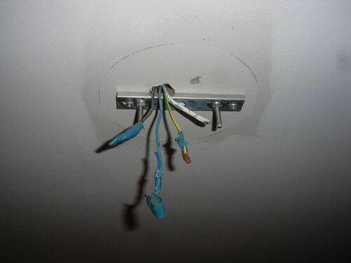 Фото 1. Монтажная рейка старой люстры, оставившей след на потолке. Налицо нарушения технологии окраски потолка. Потолочный крюк в распрямлённом состоянии.