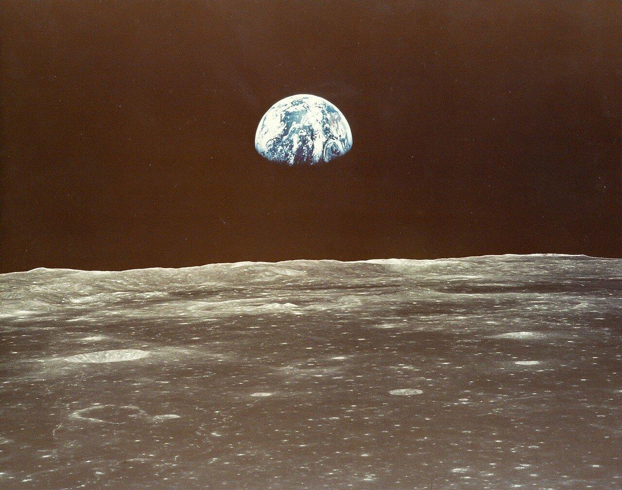 Коллинз сообщил в ЦУП, что пепельный свет Луны настолько ярок, что можно читать книгу.  На снимке: Восход Земли над лунным горизонтом.. «Аполлон-11» подлетает к Морю Смита