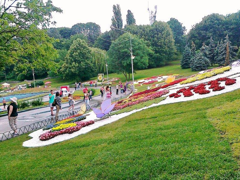 Посетители выставки цветов на Певческом поле перед композициями
