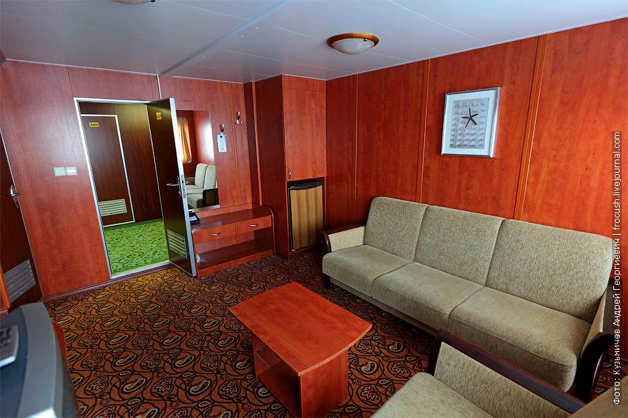 Это гостиная люкса с мягкой мебелью, журнальным столиком, шкафом-стенкой, холодильником, радио и телевизором. теплоход «Кронштадт»