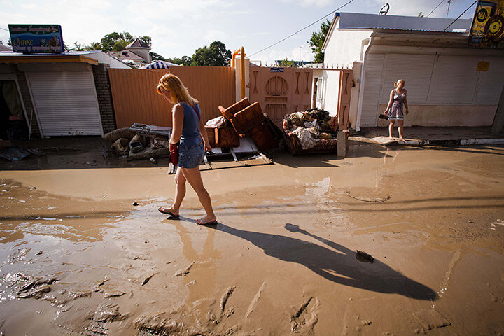 A woman walks in a muddy street in the Black Sea resort of Gelendzhik