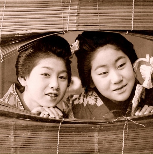 Two Maiko peek through a boken bamboo window shade in Old Japan.jpg