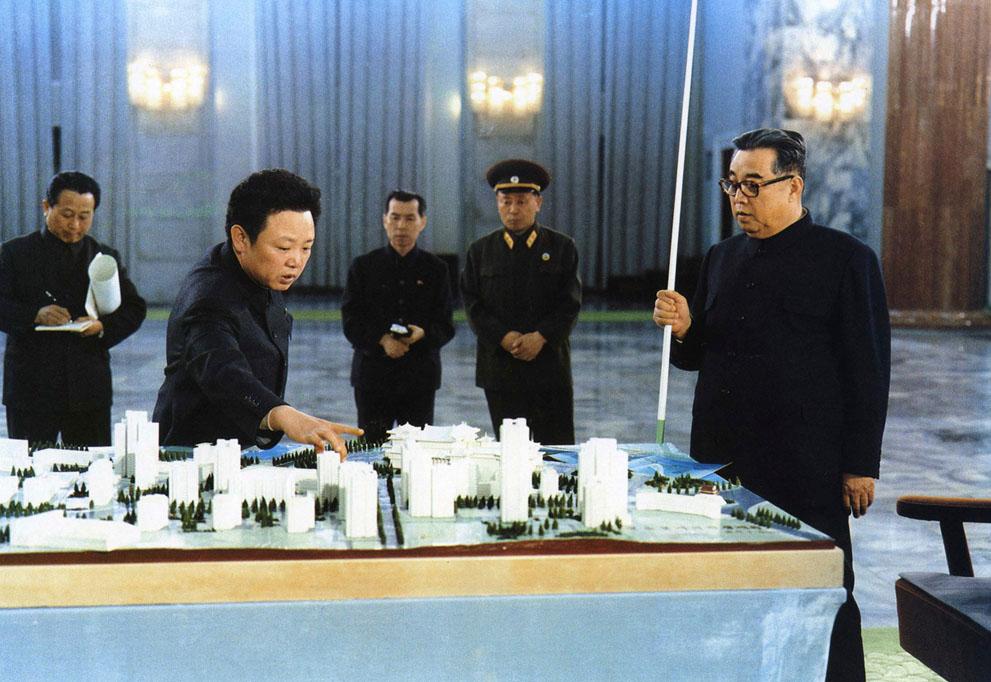 Ким Ир Сен (справа) и Ким Чен Ир (в центре) смотрят на миниатюру одной из улиц Пхеньяна в январе 1998 года.jpg