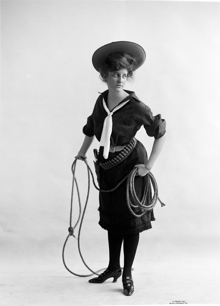 Studio portrait of a woman dressed as a cowgirl poses with a rope in her hand. 1903.