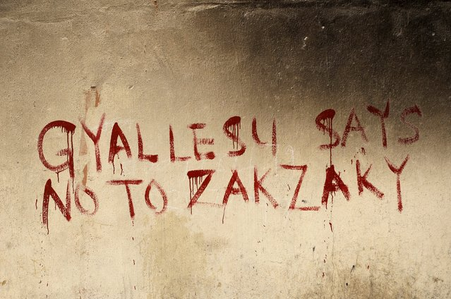 Graffiti on the walls of a house that was destroyed during clashes between Shi'ites and the arm