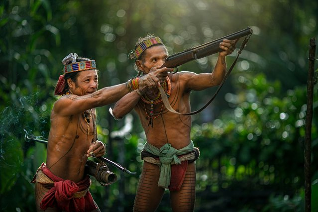 Two men of the Mentawai tribe use guns to hunt and forage for food taken on July 19, 2014 on the Men