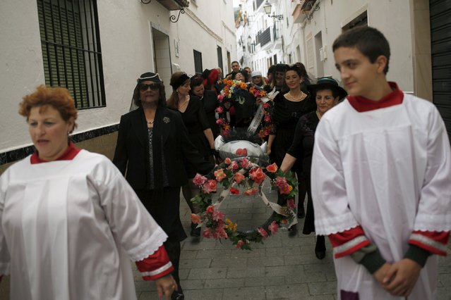 "Women dressed up as widows re-enact the traditional burial of the sardine during ""El Dia de los Polv"
