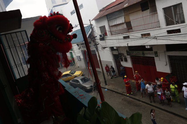 Dancers perform a lion dance on a balcony of the Yan Wo temple as locals look on during celebrations