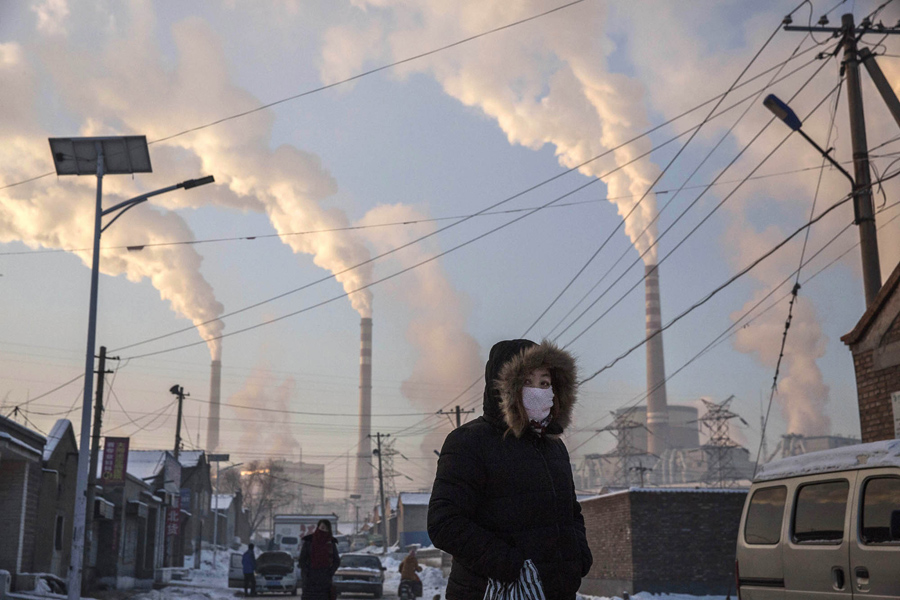 Smoke billows from stacks, as a Chinese woman wears a mask while walking in a neighborhood next to a