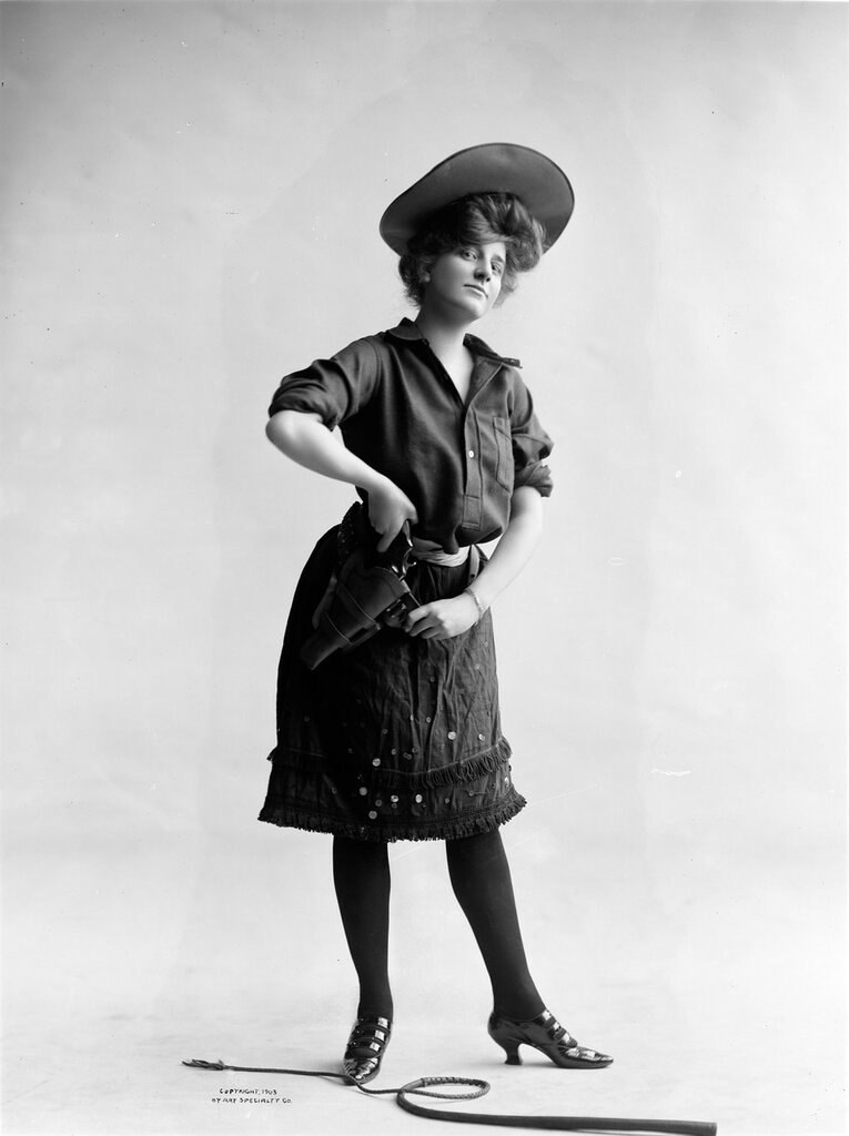 Studio portrait of a woman dressed as a cowgirl. She pulls a gun from the holster. A whip is on the ground at her feet.1903.