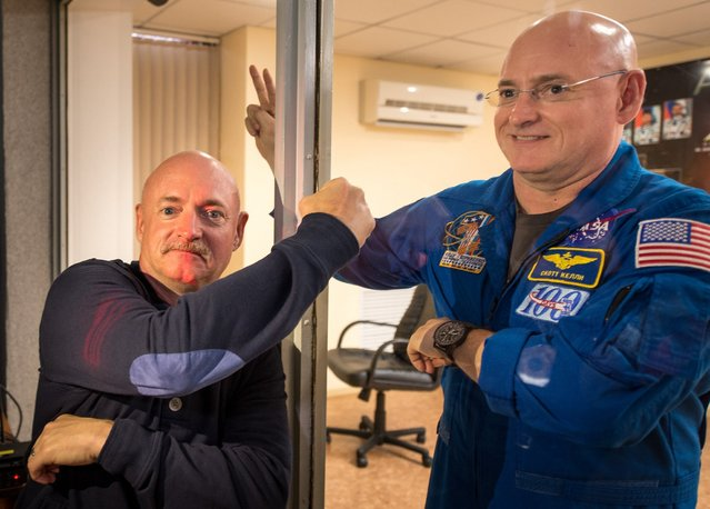 Retired NASA Astronaut Mark Kelly, left, fist pumps his identical twin brother, NASA Astronaut Scott