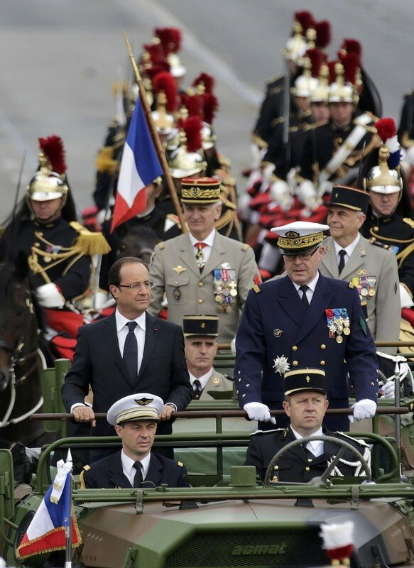 France's President Hollande stands at attention in the command car as he reviews the troops while descending the Champs Elysees in Paris at the start of the traditional Bastille Day military parade in Paris