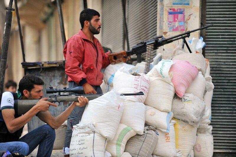 Syrian rebels take cover behind bags dur