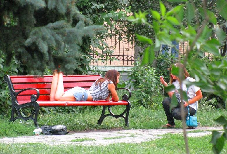 Девушка на красной скамейке в киевском парке