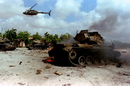 A U.S. army helicopter hovers over Somali warlord Mohammed Farrah Aideed's destroyed tanks in Mogadishu
