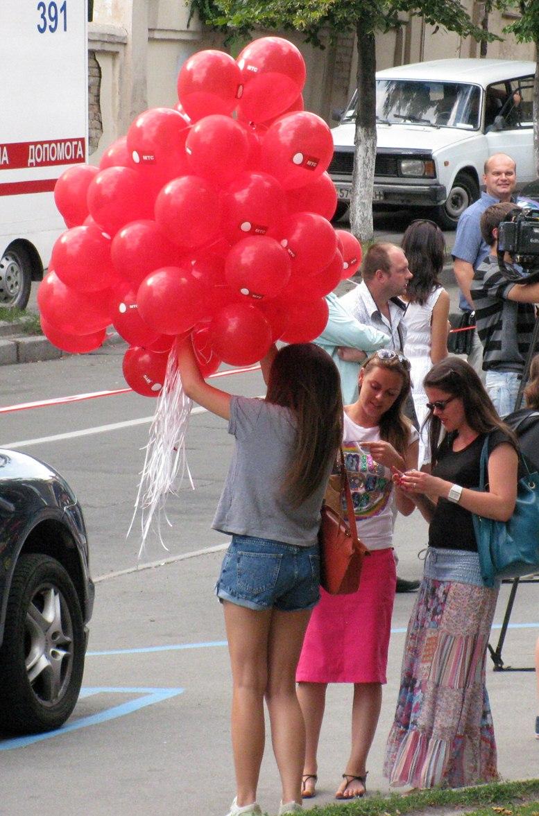 Красные воздушные шары в руках у девушки на улицах Киева