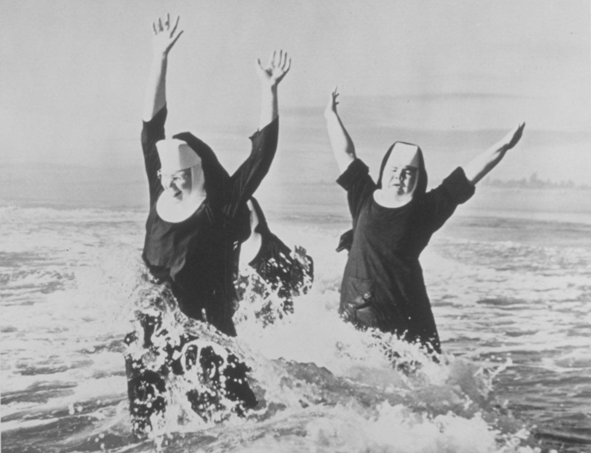Июль 1949 года. Две сестры веселятся в океане в своих робах.