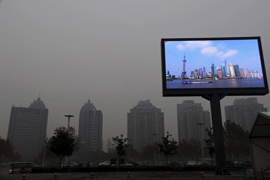 A screen showing Pudong financial area in a clear day is seen amid heavy smog in Zhengzhou, Henan pr