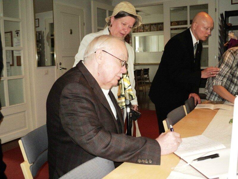 Начальник РИС-О Г.А. Фёдоров расписывается в книге почётных посетителей храма Преображения Господня города Порвоо