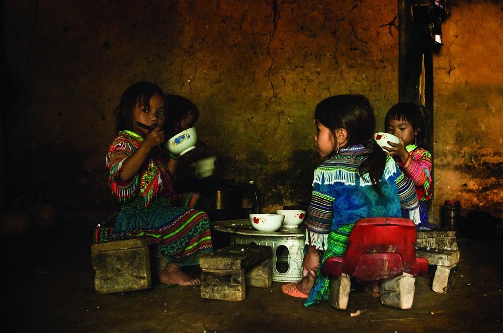 Дети едят в доме в деревне Бак Ха.