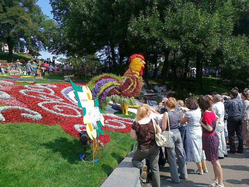 Посетители выставки цветов рассматривают инсталляцию