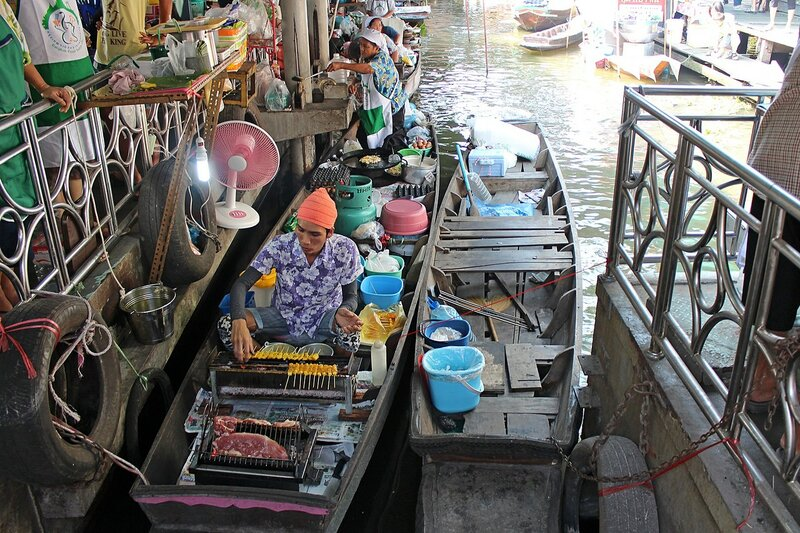 Изготовление и продажа с лодки мяса на гриле на плавучем рынке Талинг Чан, Бангкок, Таиланд