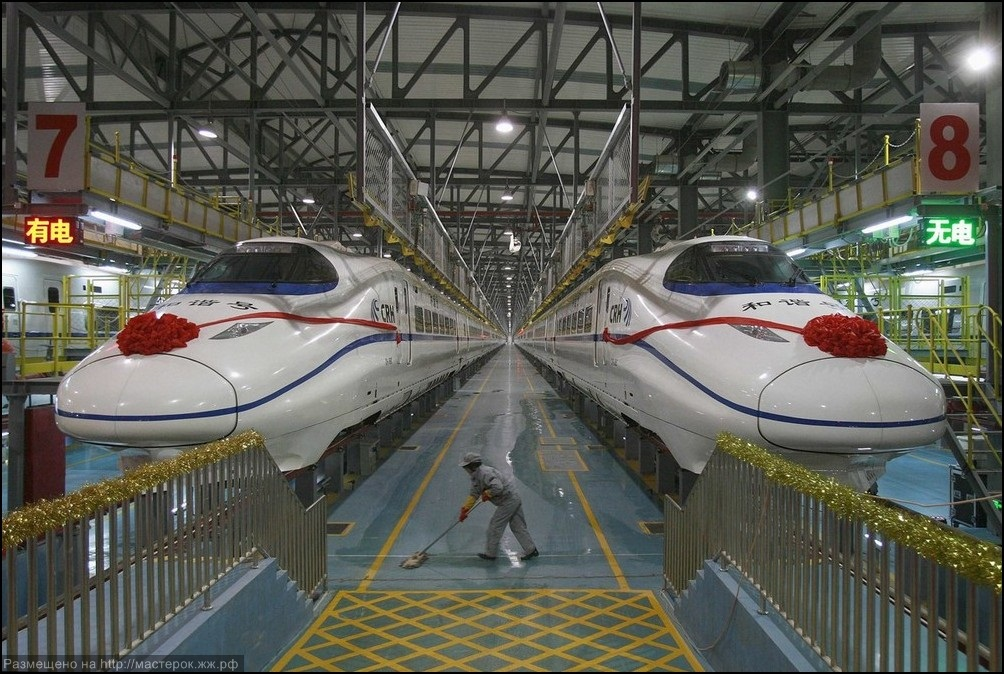 A labourer cleans the floor beside a China Railway High-speed train preparing for the operation ceremony from Wuhan to Guangzhou in Wuha n
