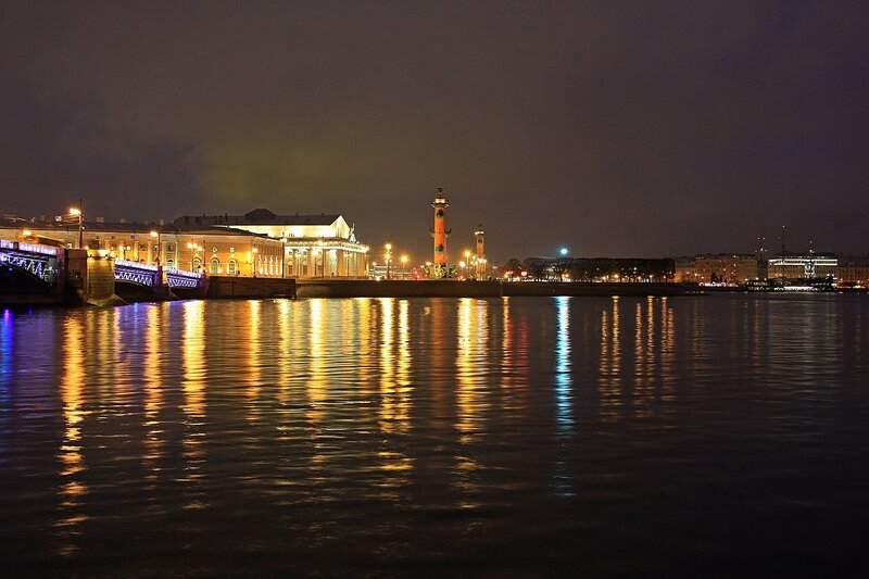 Отражение ночных огней стрелки Васильевского острова в реке Неве. Дворцовый мост, здание Биржи и ростральные колонны.