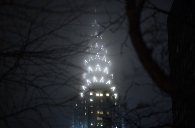 The Art Deco top of the Chrysler Building is seen through the fog in Midtown New York on December 17