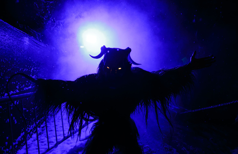 A participant dressed as the Krampus creature scares onlookers during the Krampus gathering in Goric