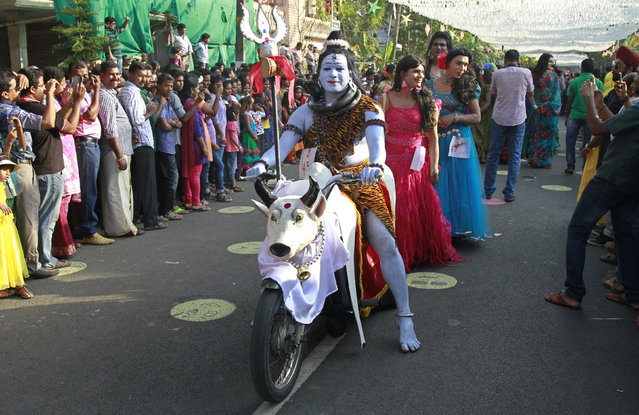 A performer dressed as Shiva sits on a motorcycle as he participates in the 30th Cochin Carnival at