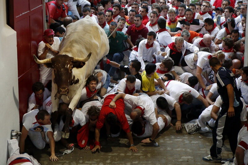 A steer jumps over the crowd of runners blocking the entrance to the bullring during the second running of the bulls of the San Fermin festival in Pamplona