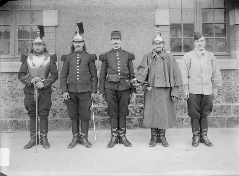 Cinq soldats presentant cinq variations de l'uniforme du regiment de cuirassier posent le long du mur de la caserne.