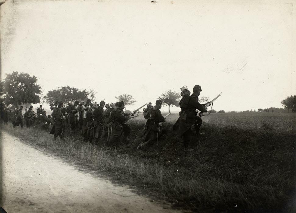 Des fantassins, en tenue de mobilisation et armes de fusils modele Berthier 1907, executent un assaut.