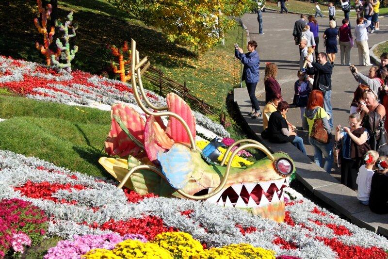 Посетители выставки фотографируют цветочную композицию